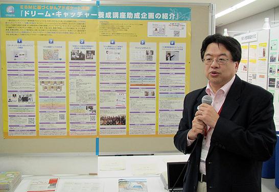 ポスターの前で、ドリーム・キャッチャー養成講座助成企画について解説するマイ・オンコロジー・ドリーム実行委員長の上野氏